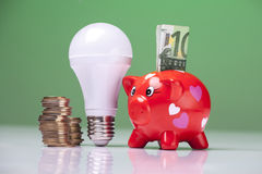 The right thing. Piggy bank and savings going from the use of LED light bulbs Stock Photography