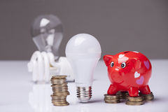 The right thing. Piggy bank and savings going from the use of LED light bulbs royalty free stock images