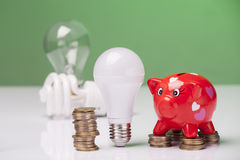 The right thing. Piggy bank and savings going from the use of LED light bulbs Stock Photo