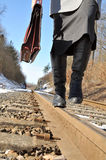 On the right track. Woman with a briefcase walking on rails Royalty Free Stock Photography