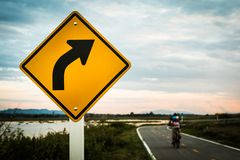 Right turn sign. The backdrop has a cyclist on the road. There is an evening sky and river royalty free stock image