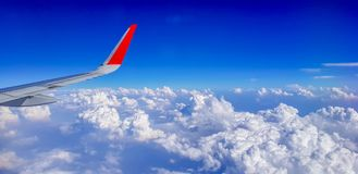 Right wing of jet plane over cloudy sky. Right wing of jet plane with red wingtip over cloudy sky Stock Photo