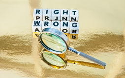 Right or wrong. Text right or wrong in black uppercase letters inscribed on small white cubes with hand magnifier to symbolize deciding which is right and which Stock Image