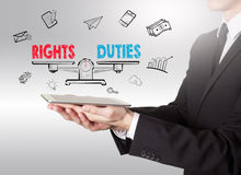 Rights and Duties balance, young man holding a tablet computer Royalty Free Stock Photography