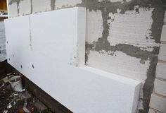 Rigid extruded polystyrene house wall insulation. Insulating house aerated concrete blocks wall with rigid styrofoam outdoors. Rigid extruded polystyrene house royalty free stock image