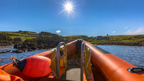 Rigid inflatable boat sunny day. Rigid inflatable boat out on sea near an island on a sunny day Stock Photos