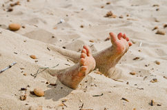 Rigor mortis on the beach. Two feet on the beach in rigor mortis protrude from the sand Stock Images