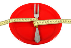 Rigorous Diet_2. Ceramic plate with fork and measuring tape. Symbolize a diet and the control over meal Royalty Free Stock Photography