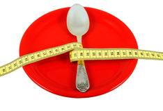 Rigorous Diet_3. Ceramic plate with spoon and measuring tape. Symbolize a diet and the control over meal Royalty Free Stock Photos
