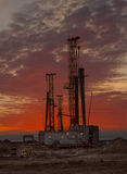 Rigs at dawn. Drilling rigs working in the wilderness, they make technological wells Stock Image