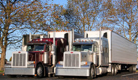 Rigs under trees. Two rigs, silver and red parked under trees taking a break Royalty Free Stock Image