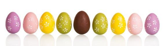 Rij kleurrijke die paaseieren in centrumchocolade, op wit wordt geïsoleerd stock foto