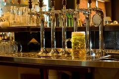 Rij van bierkranen in een bar met een kroes van bier Stock Fotografie