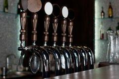 Rij van bierkranen op een roestvrij staalvaatje in een bar royalty-vrije stock afbeeldingen