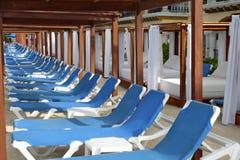 Rij van blauwe ligstoelen Stock Foto's