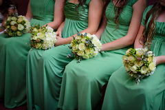 Rij van bruidsmeisjes met boeketten bij huwelijksceremo Stock Foto's