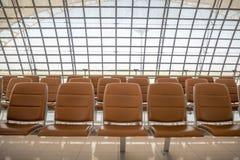 Rij van comfortabele bruine zetels voor het wachten in luchthaven op achtergrond royalty-vrije stock fotografie