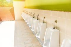 Rij van de blokken van het urinoirtoilet voor de mens op betegelde muur royalty-vrije stock fotografie
