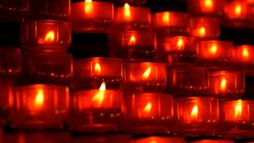 Rij van de christelijke brandwond van gebed rode ronde votive kaarsen in dark Gebed die Offerkaarsen dicht omhoog aansteken burni stock footage