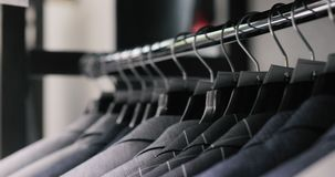 Rij van de jasjes van het mensenkostuum op hangers Inzameling van nieuwe mooie kleren die op hangers in een winkel hangen stock videobeelden
