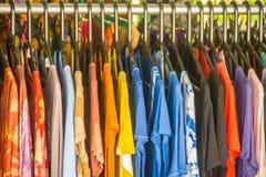Rij van de kleren die van de de zomerverkoop op het rek hangen Manierkleren op Verkoop stock afbeelding