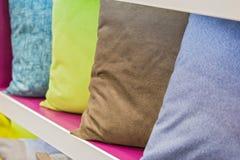 Rij van decoratieve hoofdkussens op een opslagplank Leerhoofdkussen stock afbeelding