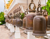 Rij van Doorstane Bronsklokken in Boeddhismetempel, Thailand royalty-vrije stock foto