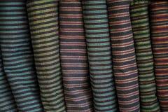 Rij van fatsoenlijke traditionele de stoffen textielbroodjes van het strookpatroon in lokale winkel stock afbeeldingen
