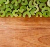 Rij van gehakte selderiestukken tegen hout Royalty-vrije Stock Fotografie