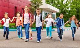Rij van gelukkige jonge geitjes met zakken dichtbij de schoolbouw stock afbeeldingen