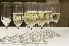 Rij van glazen met gegoten champagne stock foto