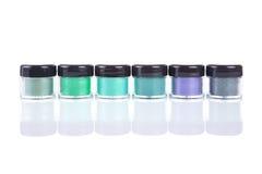 Rij van groene minerale oogschaduwwen in duidelijke plastic kruiken Stock Fotografie