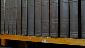 Rij van grote oude zwarte boeken op een boekenrek in bibliotheek stock video