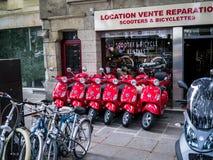 Rij van het heldere rode scooters geparkeerde buitenhandel drijven op stoep in Parijs Royalty-vrije Stock Fotografie