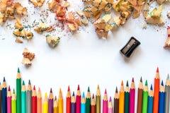 Rij van kleurpotloden en potloodscheerbeurten op een document royalty-vrije stock afbeeldingen