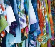 Rij van kleurrijke gevormde T-shirts die omhoog hangen Stock Foto's