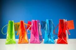Rij van kleurrijke zakken tegen de blauwe achtergrond Royalty-vrije Stock Foto