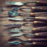 Rij van kunstenaarspalet knifes op oude houten lijst Stock Foto