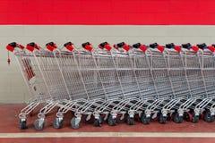Rij van lege boodschappenwagentjes in supermarkt Stock Foto's