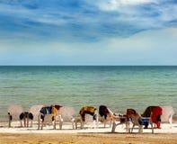 Rij van ligstoelen op de kustlijn stock afbeelding