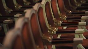 Rij van luxueuze stoelen met rode kussens in lege concertzaal stock videobeelden