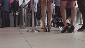 Rij van mensen die in een luchthaven wachten Voeten mensen in lijn bij de luchthaven stock fotografie