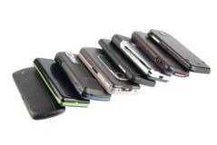 Rij van moderne mobiele telefoons op wit Stock Afbeeldingen