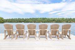 Rij van Muskoka-stoelen op een dok die op het meer kijken stock foto