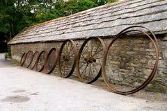 Rij van oude landbouwbedrijfwielen die tegen een rustiek oud steengebouw leunen Stock Foto's
