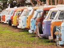 Rij van overledde kleurrijke en gereduceerde troosteloze bestelwagens stock fotografie
