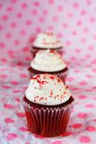 Rij van rood fluweel cupcakes stock foto