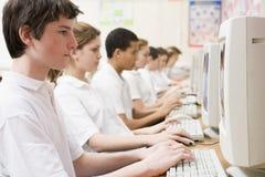 Rij van schoolkinderen die op computer bestuderen stock afbeelding