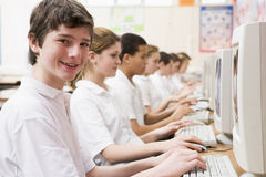 Rij van schoolkinderen die op computer bestuderen stock afbeeldingen