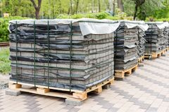 Rij van stapels van grijze bestratingsplak op houten basis Concrete steen het bedekken vlag Geïsoleerd op wit stock foto